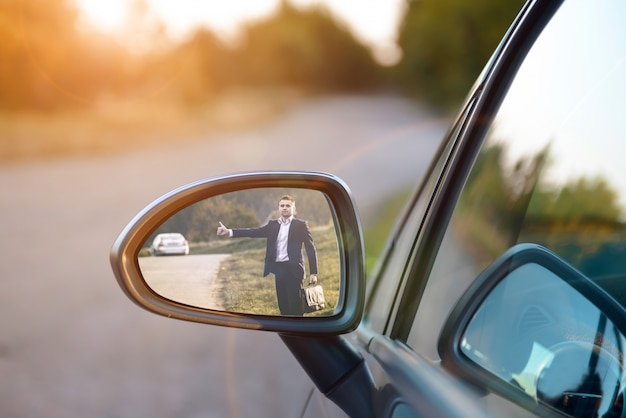 Hitchhiking man in the rearview mirror