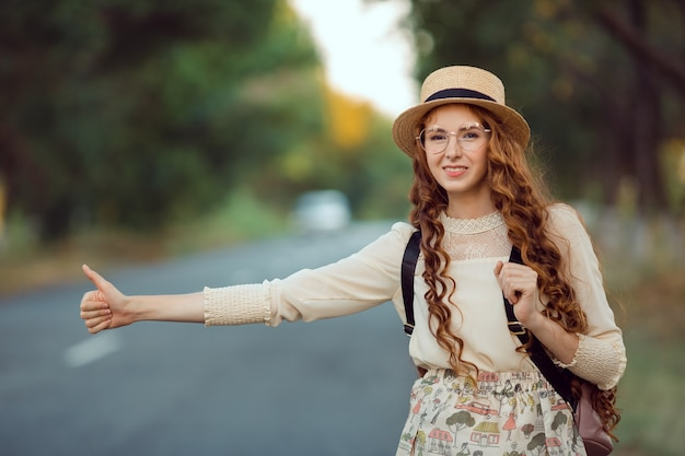 ヒッチハイク観光のコンセプト。休暇旅行中に道路を歩く帽子とバックパックを持つ旅行ヒッチハイカーの女性の肖像画