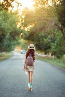 ヒッチハイク観光のコンセプト。休暇旅行中に道路を歩く帽子とバックパックを持つ旅行ヒッチハイカーの女性