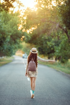 Hitchhiking tourism concept. travel hitchhiker woman with hat and backpack walking on road during holiday travel
