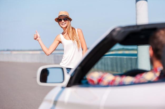乗り物をひっかける。フォアグラウンドで車と道路の脇でヒッチハイクの美しい若いファンキーな女性