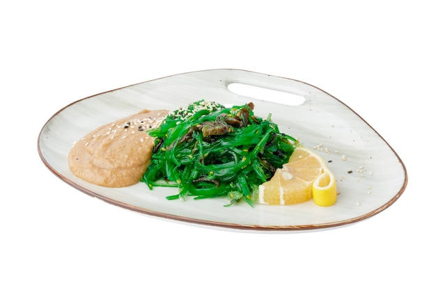 Салат хияши вакаме чука с ореховым соусом, изолированные на белом