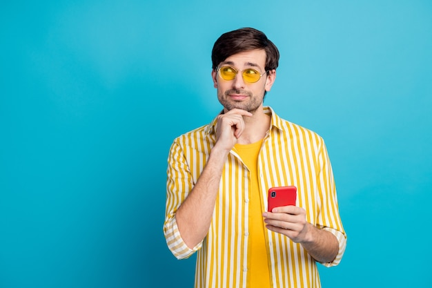 Hmm decide summer resort. minded man traveler use smartphone look copyspace think thoughts choose social media travel ads wear yellow white clothes isolated over blue color background