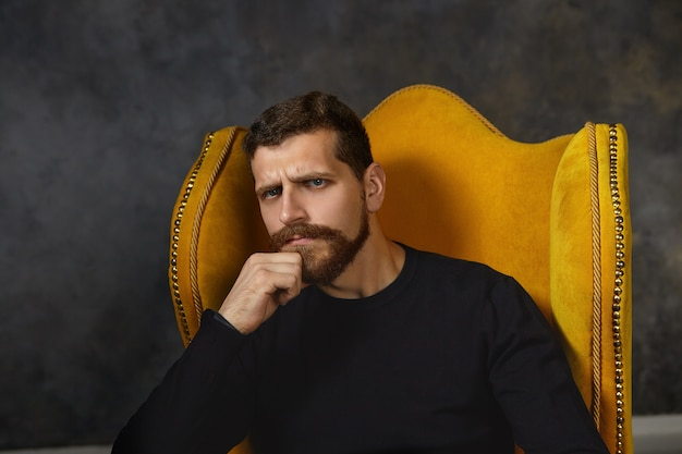 Hmm. doubtful unshaven man frowning while hesitating about some decision, sitting in armchair indoors alone, rubbing beard, searching for perfect solution or idea, feeling doubtful and frustrated