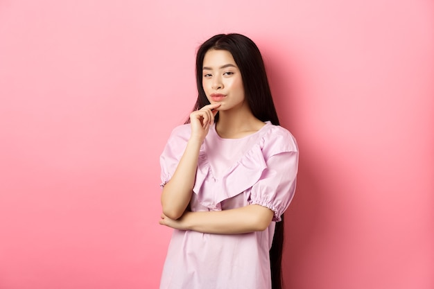 Hmm, interesting. pensive and cunning asian girl having idea, plan to do something, looking at camera and touching chin with thoughtful face, standing on pink background.