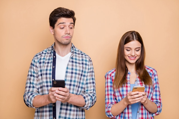 Hmm interesting.... portrait of pensive guy use his smartphone watch who secret admirer his wife chatting on social network account wear checkered shirt isolated over beige color background