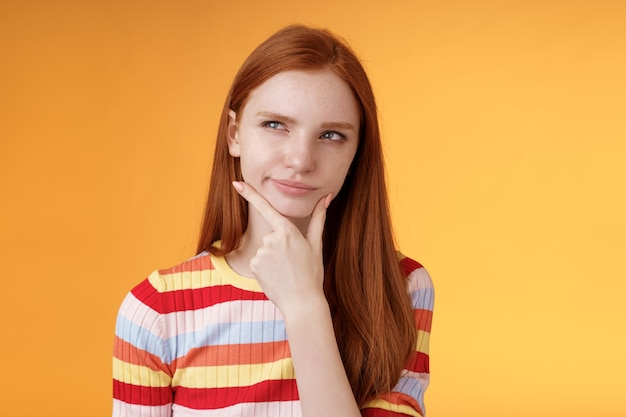 Hmm interesting. suspicious doubtful attractive european redhead female pondering choice look hesitant thoughtful touch chin smirking tricky look upper left corner thinking, take decision.
