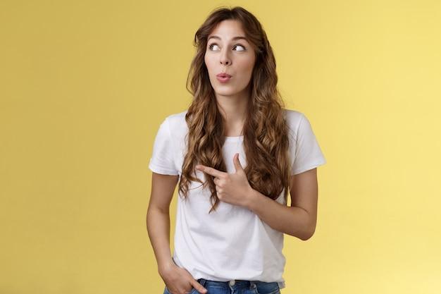 うーん面白いすごい。好奇心旺盛な愚かなかわいいきれいな女性の長い巻き毛の髪型折りたたみ唇の賞賛は、左上隅を指している新しいメニューの外観を試してみてください興味をそそられる黄色の背景に魅了されました。