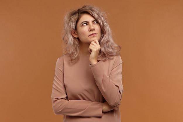 Хм. дай мне подумать. эмоциональная модная кавказская девушка с пирсингом на лице, хмурясь, с подозрительным или сомнительным видом, держась за подбородок