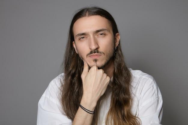 Хм. дай мне подумать. изолированный снимок серьезного сконцентрированного стильного молодого бородатого длинноволосого человека в белой формальной рубашке, прищуривающегося и держащего руку за подбородок, с подозрительным выражением лица