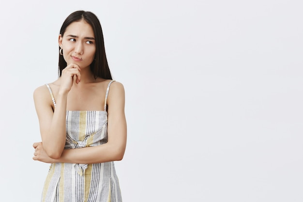 Hmm, let me think. portrait of doubtful good-looking asian female in matching trendy outfit, smirking and gazing right while holding hand on chin, thinking, hesitating over gray wall