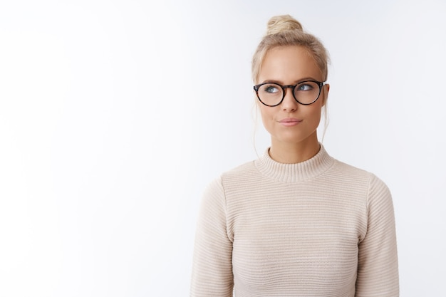 Hmm nice idea. indoor shot of devious and mysterious good-looking female with blond hair in bun wearing glasses smirking joyfully gazing dreamy at upper left corner, thinking having plan