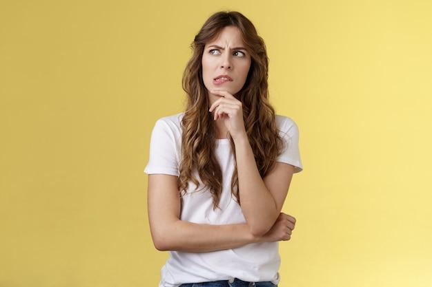 うーん、どうすればいいですか。思いやりのある強烈なスマートクリエイティブハンサムな女の子は、どのように良い行動をするかを考えています噛む唇眉をひそめているしかめっ面強烈なタッチあごを考えて選択を重要な決定をします