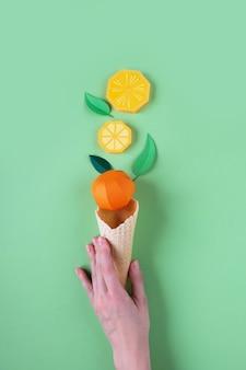 緑の表面に紙の果実とワッフルコーンを保持しているhnd