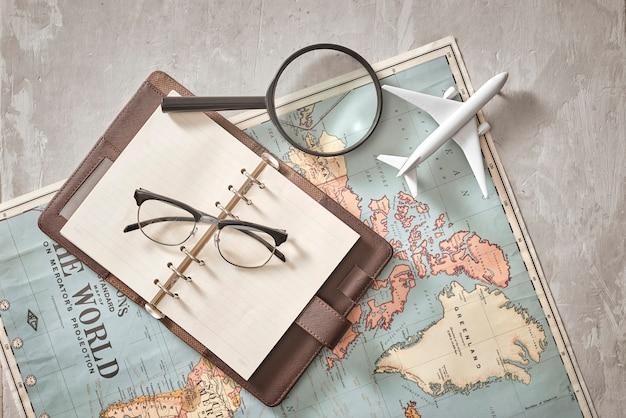 ホーチミン市、ベトナム-2018年9月22日:テキストや広告を配置できるノートブックの空の空白。飛行機、虫眼鏡、地図上の眼鏡。ロマンチックな旅行