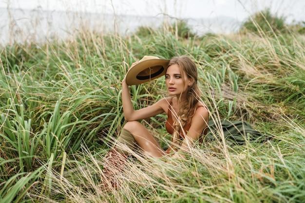 野生のステップパイを探索のバックパックと肖像画幸せな若い女。帽子と自由ho放に生きるスタイルの服でスタイリッシュな内気な少女。旅行と放浪癖。素晴らしい大気の瞬間