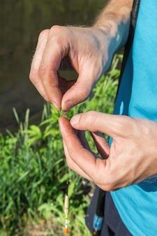 취미 및 활동적인 레크리에이션 한 남자가 물고기를 잡기 위한 미끼로 벌레를 갈고리에 꽂습니다.