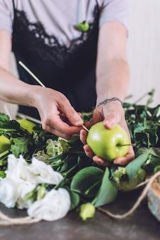コロナウイルス中の趣味や活動、芸術品や工芸品。花屋の女性は果物の食用花束を作ります。自然さ、フラワーアレンジメント、花屋のトリック、ヒント、トレンド。