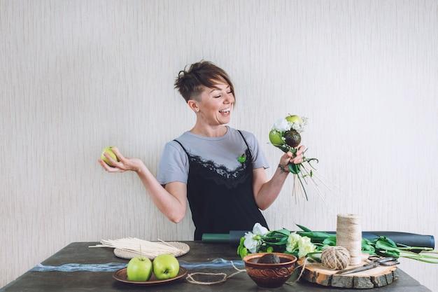 コロナウイルスの花屋の女性の間の趣味と活動の芸術品と工芸品は果物の食用の花束を作ります