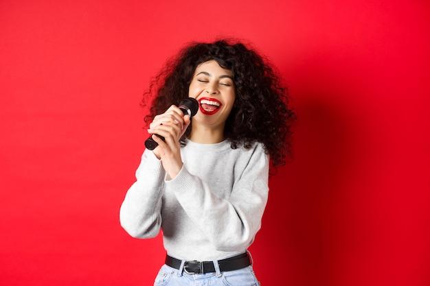 趣味とレジャーの概念。幸せな女性がマイクで歌を歌い、マイクとカラオケを楽しんで、赤い背景の上に立っています。