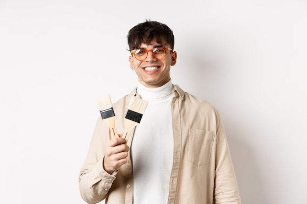 Хобби и досуг концепция. стильный молодой человек в очках показывает кисти и улыбается, приглашая что-то нарисовать, стоя на белом фоне.