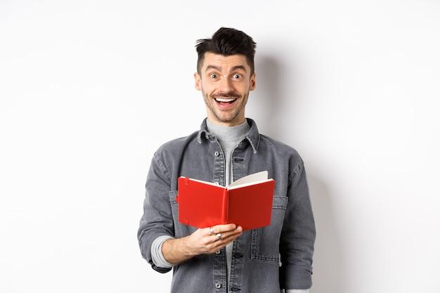 취미와 여가. 행복 한 젊은 남자 플래너를 읽고, 일기 또는 빨간색 저널을 들고 웃 고, 메모를 만들고, 흰색 배경에 서.