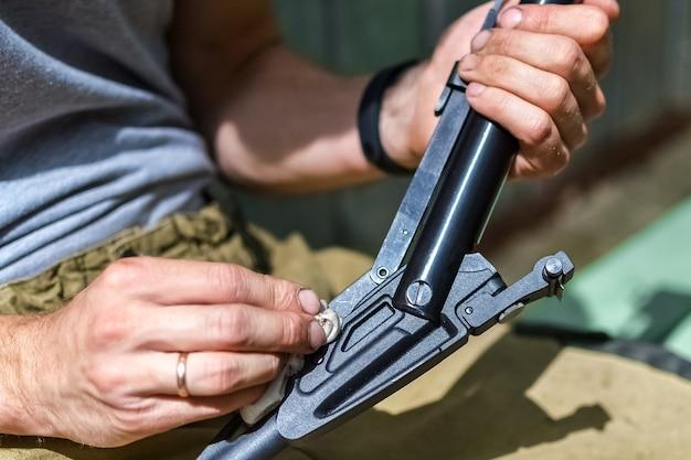 취미 및 야외 레크리에이션 한 남자가 펜치로 공기총을 수리하고 촬영을 위해 준비합니다