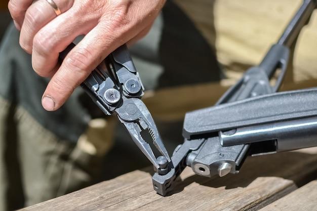 취미 및 야외 레크리에이션 한 남자가 헝겊으로 공기총을 닦고 촬영을 위해 준비합니다