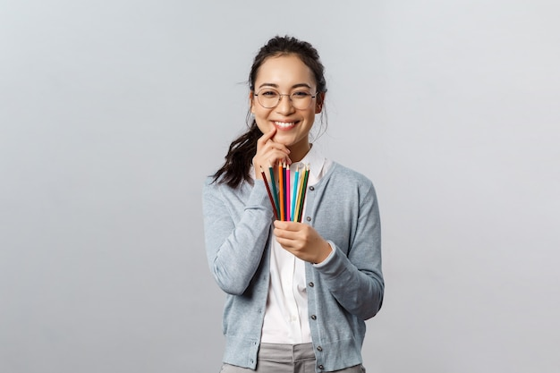Hobbies, creativity and art concept. silly happy smiling asian woman, artist in glasses giggle as holding colored pencils, have interesting idea for her next artwork, drawing picture, grey background.