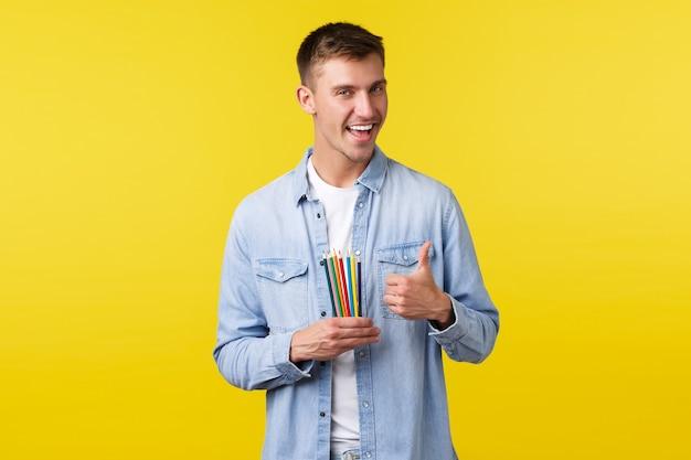 趣味、レジャー、人々のライフスタイルのコンセプト。カジュアルな服装で満足しているハンサムな男性は、親指を立てて色鉛筆を見せながら、どの描画素材が最適かをアドバイスし、描画方法を学びます。