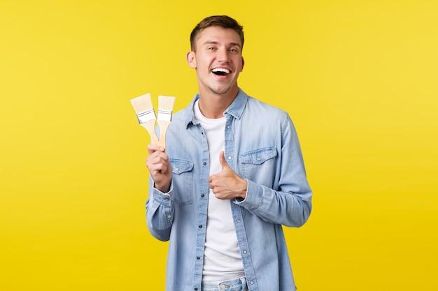 趣味、レジャー、人々のライフスタイルのコンセプト。幸せな笑顔の満足した男は、親指を立てて、2つの絵筆、立っている黄色の背景、改修の時間を見せて喜んで笑っています。