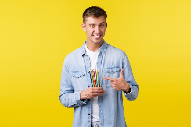 趣味、レジャー、人々のライフスタイルのコンセプト。笑顔のハンサムな若い男、高品質の色鉛筆で指を指しているアーティスト、黄色の背景に立って描画製品をお勧めします