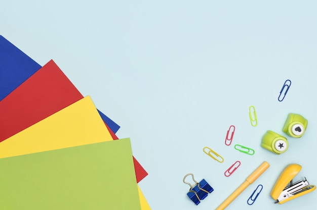 Hobbies and leisure flat lay. colourful paper sheets, paperclips, pen and creative paper punch on blue background with copy space. preschool education at home.