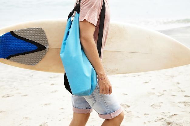 趣味、アクティブなライフスタイル、夏の休暇の概念。砂浜を歩いているバッグを持つ若い観光客のショットをトリミング