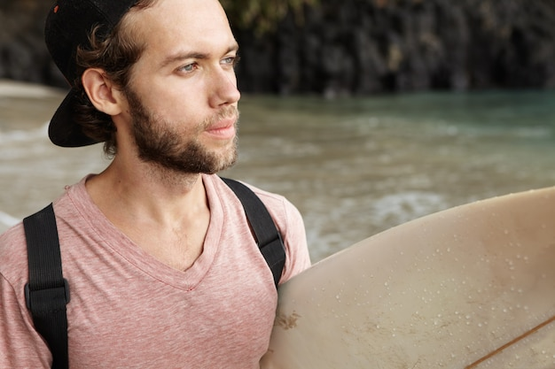 Hobby and active recreation. handsome young caucasian surfer having pensive and wistful look, holding his white surfboard, daydreaming of riding big waves