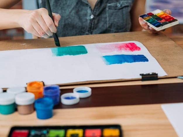 趣味と創造性。水彩で抽象的なアートワークを描いている若い女性アーティストのトリミングされたショット。