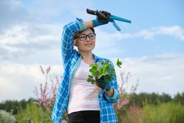 성숙한 여인의 취미와 레저, 딸기 덤불을 들고 정원 도구와 장갑에 여성.