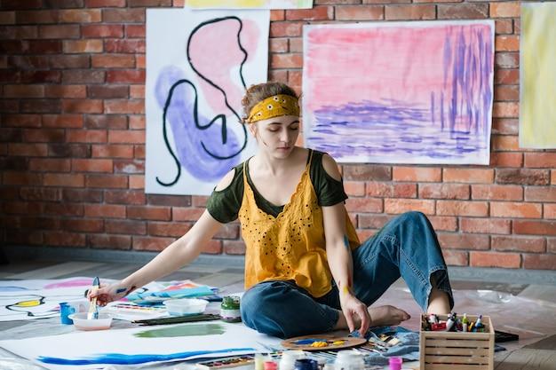 趣味とレクリエーション。床に座って、抽象的なアートワークを描いている女性アーティスト。
