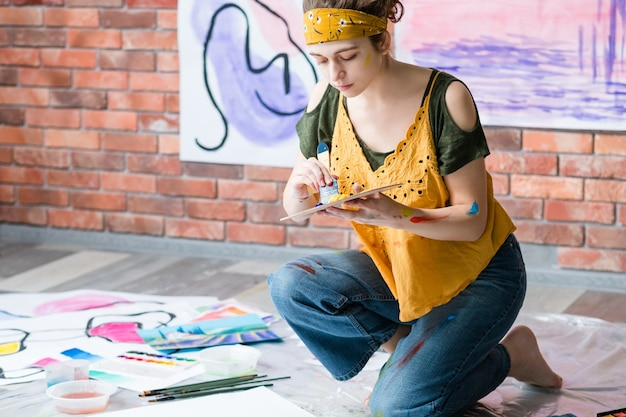 趣味とレクリエーション。床に座って、抽象的なアートワークを描く女性の側面図