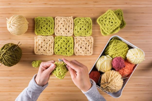 趣味、クラフト、創造性、自宅での自由時間のコンセプト。女性の手、編み物、かぎ針編み。フラットレイ、上面図