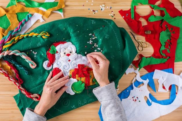 趣味、クラフト、創造性、自宅での自由時間のコンセプト。クリスマスの装飾を作る女性の手。アップリケ、ホリデーニードルクラフトを感じました。フラットレイ、上面図