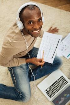 趣味。ノートパソコンで作業し、床に座って、いくつかの書類を持っている間、音楽を聴いている格好良いインスピレーションを得たアフリカ系アメリカ人の男