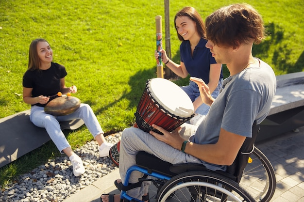 Hobby. happy handicapped man on a wheelchair spending time with friends playing live instrumental music outdoors. concept of social life, friendship, possibilities, inclusion, diversity.