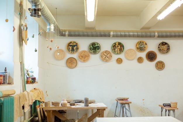 Хобби в мастерской. настоящая красивая гончарная мастерская с декоративными тарелками на стенах и рабочей мебелью.
