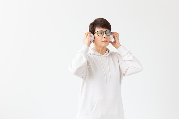 趣味、興味、人々の概念-コピースペースのある白い壁に大きなヘッドフォンで音楽を聴いている40〜50歳の美しい女性