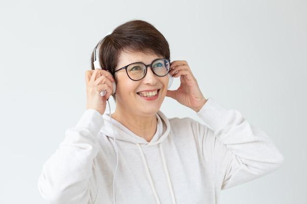 趣味、興味、人々の概念-白い壁に大きなヘッドフォンで音楽を聴いている40〜50歳の美しい女性。