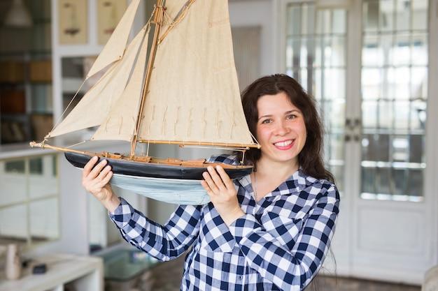 Хобби, интерьер и концепция коллекционирования - молодая женщина, держащая макет парусной лодки в комнате
