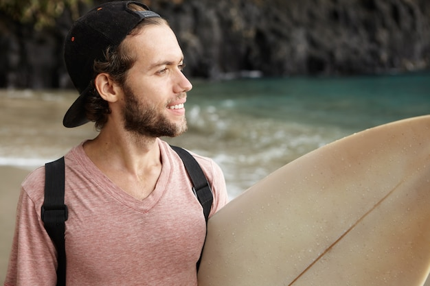 Hobby, leisure and adventure. young surfer with cute smile carrying his surf board under his arm and looking at ocean, having happy expression