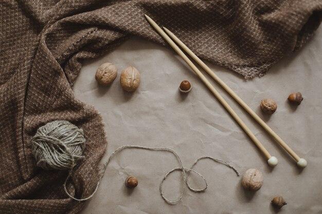 Пряжа для хобби и деревянные иглы на фоне текстуры коричневой бумаги с уютным теплым пледом ...