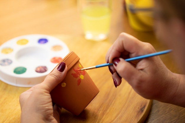 絵の具でフラワーポットを描く女性の手を描く趣味